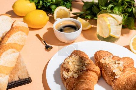 Photo pour Croissants frais, baguette, citrons et tasse de café pour le petit déjeuner sur table beige - image libre de droit