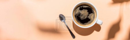 Photo for Top view of coffee cup and teaspoon on beige with shadows, horizontal concept - Royalty Free Image