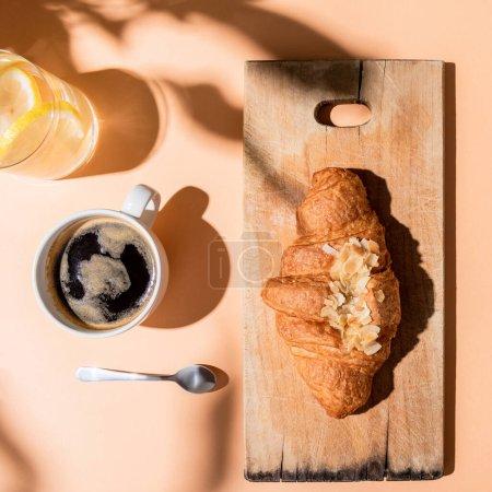 Photo pour Vue de dessus du café, de l'eau et du croissant sur planche à découper en bois pour le petit déjeuner sur table beige - image libre de droit