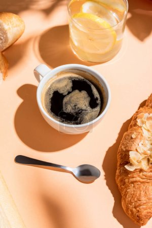 coffee, water and croissant for breakfast on beige table