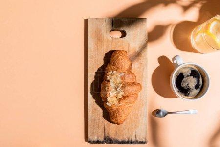 Photo pour Vue de dessus du café, de l'eau et du croissant sur planche en bois pour le petit déjeuner sur table beige - image libre de droit