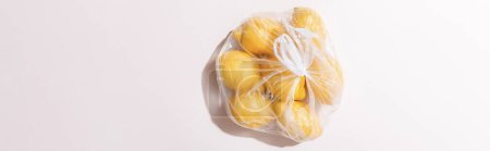 Photo for Top view of yellow lemons in plastic bag on grey table, horizontal crop - Royalty Free Image