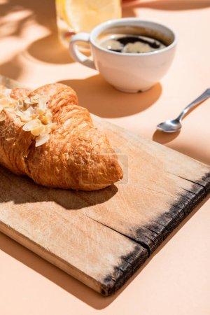 Photo pour Croissants frais sur planche à découper et tasse de café pour le petit déjeuner sur table beige - image libre de droit