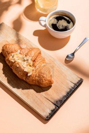 Photo pour Croissants frais sur planche de bois et tasse de café pour le petit déjeuner sur table beige - image libre de droit
