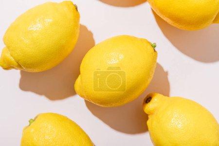 Nahaufnahme ganzer reifer Zitronen auf grauem Tisch mit Schatten
