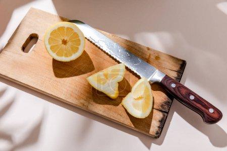 Photo pour Tranche de citron sur planche de bois sur table grise avec ombres - image libre de droit