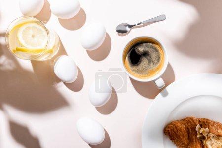 Photo pour Vue du dessus des œufs de poulet, de l'eau au citron, de la tasse à café et du croissant pour le petit déjeuner sur une table grise ombragée - image libre de droit