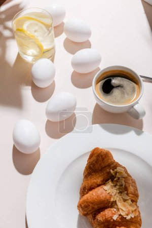 Photo for Organic boiled chicken eggs, croissant, cup of coffee and glass of water with lemon for breakfast on grey table with shadows - Royalty Free Image