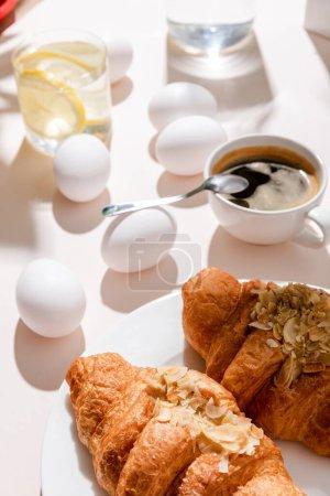 Photo pour Œufs cuits, deux croissants, une tasse de café et un verre d'eau au citron pour le petit déjeuner sur table grise avec ombres - image libre de droit