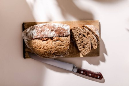 Photo for Top view of fresh baked and sliced bread on cutting board with knife on grey table with shadows - Royalty Free Image