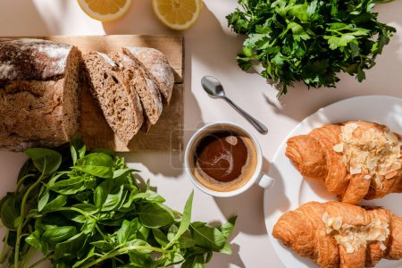 Photo for Top view of fresh croissants, bread, greenery and cup of coffee for breakfast on grey table - Royalty Free Image