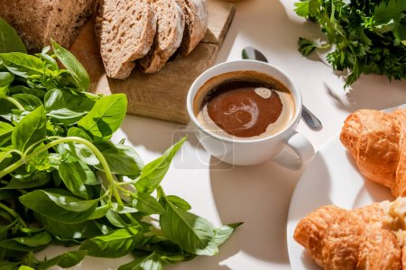 Photo for Bread, croissants, greenery and cup of coffee for breakfast on grey table - Royalty Free Image