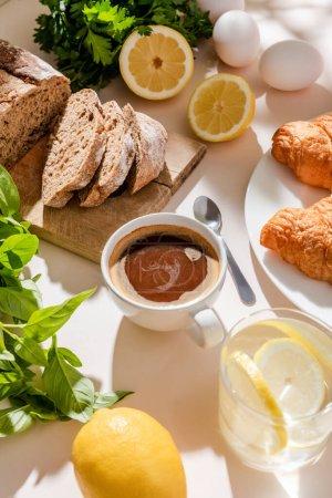 Photo pour Croissants frais, pain, verdure, oeufs, eau de citron et tasse de café pour le petit déjeuner sur table grise - image libre de droit