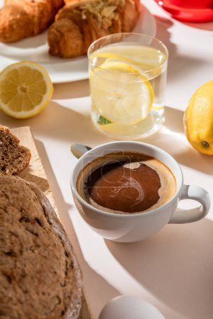 Photo for Close up of bread, lemon water and cup of coffee for breakfast on grey table - Royalty Free Image