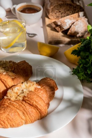 Photo for Fresh croissants, bread, coffee and lemon water for breakfast on grey table, selective focus - Royalty Free Image