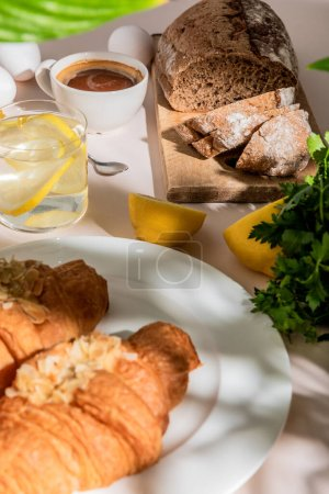 Photo for Fresh croissants, bread, eggs, coffee and lemon water for breakfast on grey table, selective focus - Royalty Free Image
