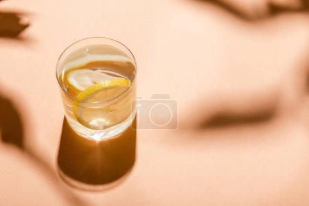 glass of fresh water with lemon slices on beige with shadows