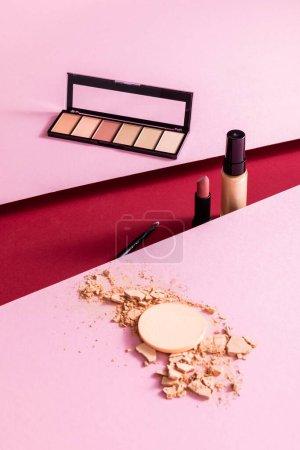 Photo pour Ombre à paupières, pinceau cosmétique, fond de teint maquillage et rouge à lèvres près de la poudre visage fissurée sur rose et cramoisi - image libre de droit