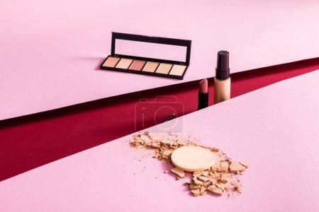 Photo pour Fond de teint maquillage, fard à paupières, rouge à lèvres et pinceau cosmétique sur fond rose et cramoisi - image libre de droit