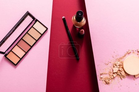 Photo for Top view of makeup foundation, cosmetic brush, lipstick and eye shadow near broken face powder on pink and crimson - Royalty Free Image