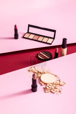 Photo pour Fond de teint maquillage, palettes de fards à paupières et rouges à lèvres près de poudre visage fissurée sur rose et cramoisi - image libre de droit