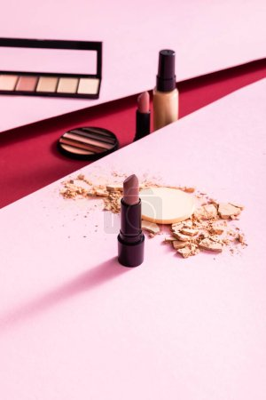 Photo for Selective focus of lipsticks, eye shadow palettes and broken face powder near face foundation on pink and crimson - Royalty Free Image