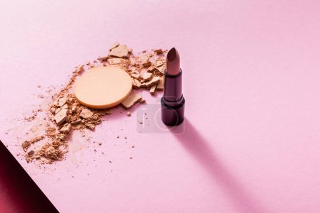 Photo for Cracked face powder near lipstick and makeup sponge on pink - Royalty Free Image
