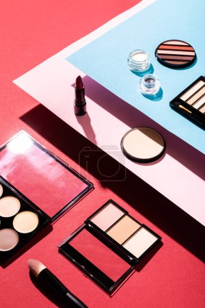 Photo for Eye shadow palettes near cosmetic brush, lipstick and face powder on crimson - Royalty Free Image