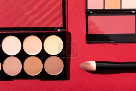 Photo for Top view of eye shadow and blush palettes near cosmetic brush on crimson - Royalty Free Image