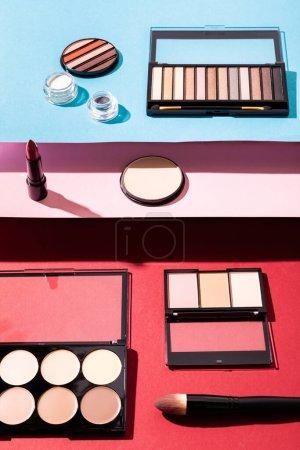 Photo pour Palettes de fard à joues et de fard à paupières près des pinceaux cosmétiques, rouge à lèvres et poudre visage sur cramoisi, rose et bleu - image libre de droit