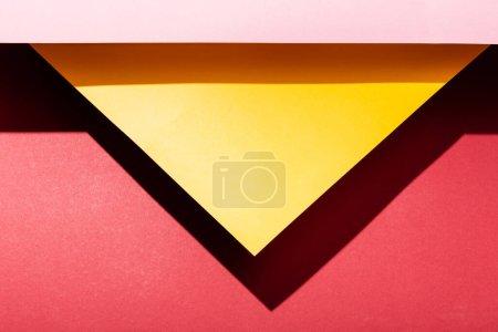 Photo pour Vue de dessus des feuilles de papier jaunes et roses vides sur cramoisi - image libre de droit