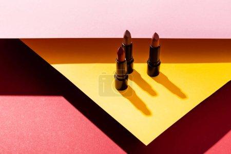 shadows near lipsticks on yellow, pink and crimson