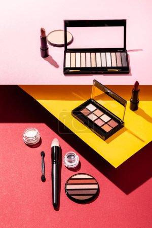 Photo pour Palettes de fards à paupières et pinceaux cosmétiques près des rouges à lèvres et de la poudre pour le visage sur cramoisi, rose et jaune - image libre de droit