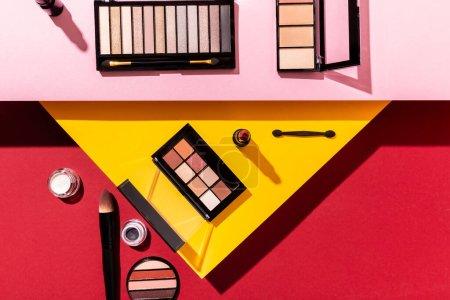 Photo pour Vue de dessus des palettes d'ombre à paupières et des pinceaux cosmétiques près du rouge à lèvres sur cramoisi, rose et jaune - image libre de droit