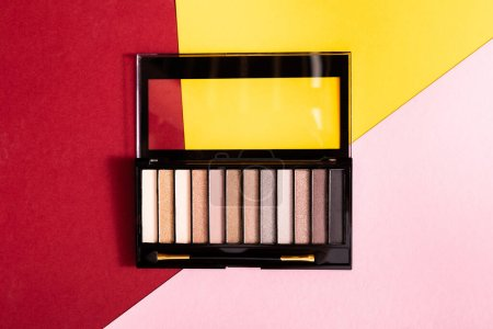 top view of eye shadow palette and double-sided eyeshadow applicator on crimson, pink and yellow