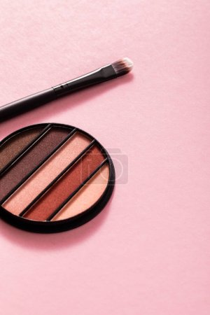 colorful and pastel eye shadow palette near cosmetic brush on pink
