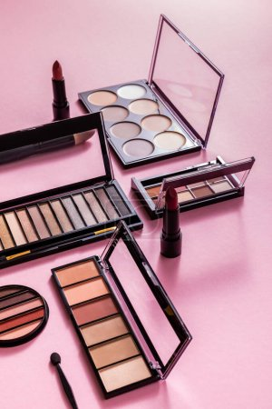 eye shadow palettes and cosmetic brushes near lipsticks on pink