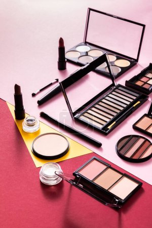 blush and eye shadow palettes near cosmetic brushes and lipsticks on pink and crimson