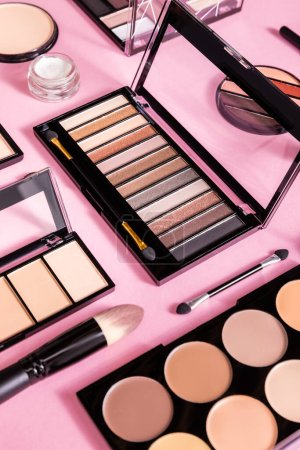 Photo for Eye shadow and blush palettes near cosmetic brushes and face powder on pink - Royalty Free Image