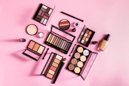 Photo for Top view of eye shadow and blush palettes near face powder, cosmetic brushes, lipsticks and face foundation on pink - Royalty Free Image