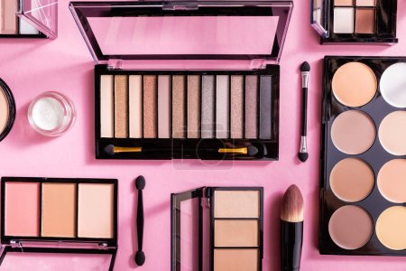 Photo for Top view of eye shadow and blush palettes near cosmetic brushes on pink - Royalty Free Image