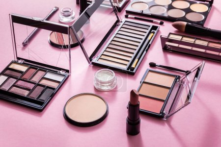 eye shadow and blush palettes near face powder, cosmetic brushes and lipstick on pink