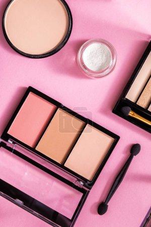 Photo pour Vue de dessus de la poudre visage et du fard à joues près de la palette des ombres sur rose - image libre de droit
