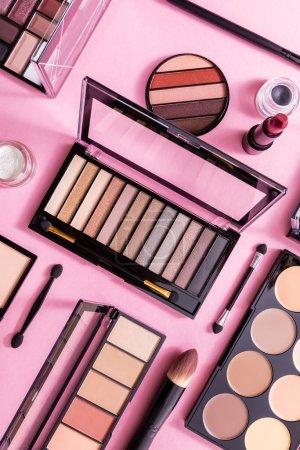 Photo pour Vue du haut du rouge à lèvres, pinceaux cosmétiques et fard à joues près de la palette ombre à paupières rose - image libre de droit