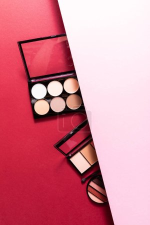 Photo for Top view of pastel eye shadow and blush palettes on pink and crimson - Royalty Free Image