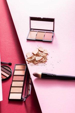 Photo pour Fard à paupières et palettes blush près de la poudre pour le visage fissurée et pinceaux cosmétiques sur rose et cramoisi - image libre de droit