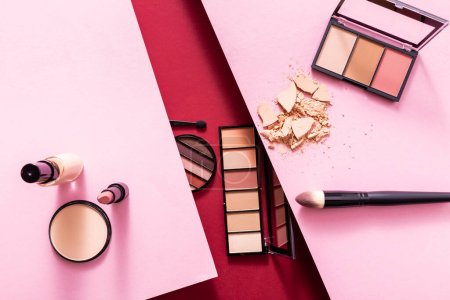 Photo for Top view of eye shadow and blush palettes near cracked face powder, face foundation, lipstick and cosmetic brushes on pink and crimson - Royalty Free Image