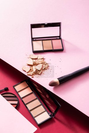 Photo pour Palettes ombre à paupières près de poudre craquelée visage et pinceaux cosmétiques sur rose et cramoisi - image libre de droit
