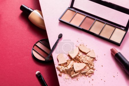 Photo for Face foundation near eye shadow palette, cracked face powder, cosmetic brushes and lipstick on pink and crimson - Royalty Free Image