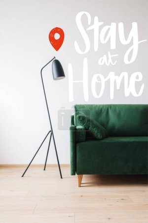 Photo for Green sofa with pillow near modern floor lamp and stay at home lettering - Royalty Free Image